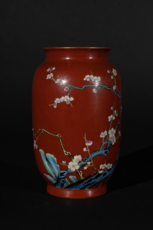Arte Cinese  A porcelain red ground vase painted with blossoming cherry tree branches and bearing a Qianlong six character seal mark at the base China, 20th century .