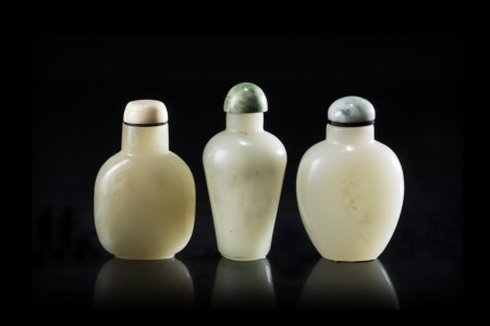 Tre snuff bottles in giada color celadon, di varie forme, con coperchio in...